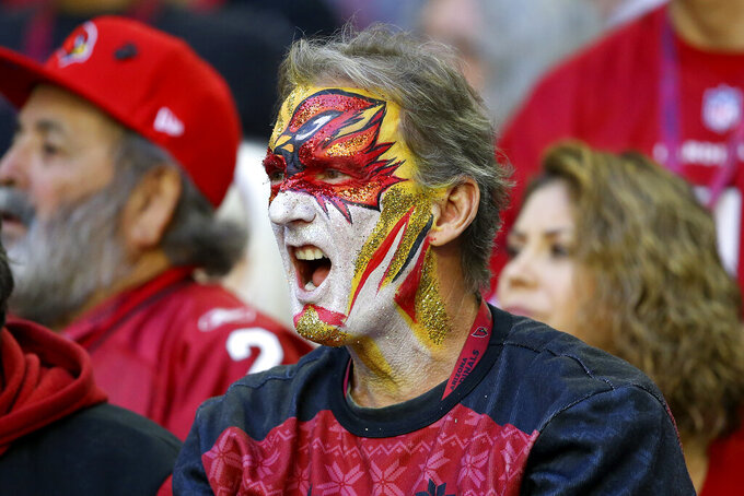 An Arizona Cardinals fan cheers during the first half of an NFL football game against the Los Angeles Rams, Sunday, Dec. 1, 2019, in Glendale, Ariz. (AP Photo/Ross D. Franklin)