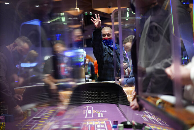 FILE - In this March 25, 2021, file photo, people play craps while wearing masks and between Plexiglas partitions as a precaution against the coronavirus at the opening night of the Virgin Hotels Las Vegas in Las Vegas. Las Vegas is bouncing back to pre-coronavirus pandemic levels, with increases in airport passengers and tourism and casinos statewide reporting $1 billion in winnings last month for the first time since February 2020. (AP Photo/John Locher, File)