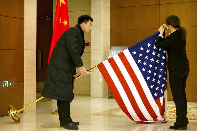 FILE - In this Feb. 14, 2019, file photo, Chinese staffers adjust a U.S. flag before the opening session of trade negotiations between U.S. and Chinese trade representatives at the Diaoyutai State Guesthouse in Beijing. China is delaying the renewal of press cards for at least five journalists working at four U.S. media outlets, an organization of foreign correspondents said Monday, Sept. 7, 2020 making them vulnerable to expulsion in apparent retribution for Washington's targeting of Chinese reporters working in the United States. (AP Photo/Mark Schiefelbein, Pool, File)