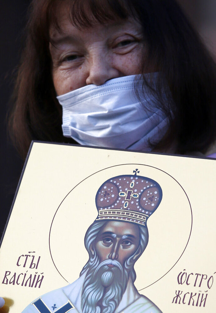 A woman holds an icon during a protest after arrest of the Serbian Orthodox Church priests in Montenegro, in Belgrade, Serbia, Thursday, May 14, 2020.  Montenegrin police said Thursday they have detained around 60 people following clashes at protests demanding the release of eight Serbian Orthodox Church priests jailed for leading a religious procession despite a ban on gatherings related to the new coronavirus outbreak. (AP Photo/Darko Vojinovic)