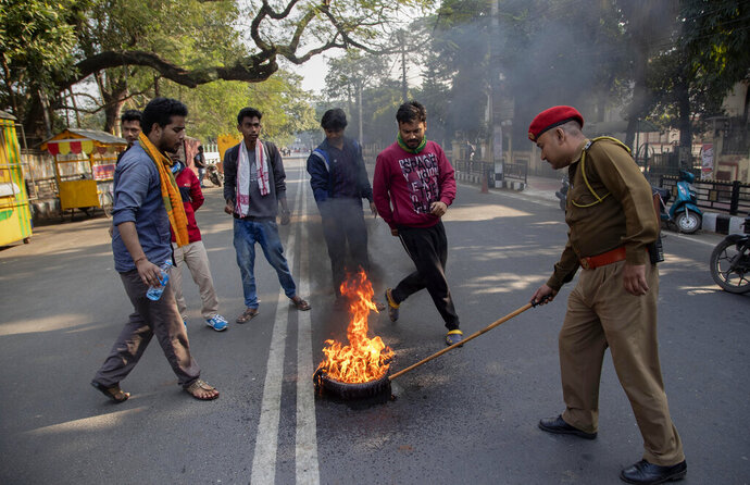 A policeman tries to douse a fire set by students during a shutdown protest against the Citizenship Amendment Bill (CAB) in Gauhati, India, Tuesday, Dec. 10, 2019. Opponents of legislation that would grant Indian citizenship to non-Muslim illegal migrants from Pakistan, Bangladesh and Afghanistan have enforced an 11-hour shutdown across India's northeastern region. (AP Photo/Anupam Nath)