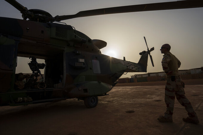 A French Barkhane force soldier inspects a Caiman transport helicopter before going on a night mission in Gao, Mali Monday June 7, 2021. After France suspended joint military operations with Malian forces after the junta led by Col. Assimi Goita retook control of Mali's transitional government May 24 2021, French President Emmanuel Macron announced at a press conference Thursday June 10, 2021 that operation Barkhane would end and be replaced by support for local partners and counter terrorism. (AP Photo/Jerome Delay)