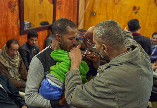 Romany, a Coptic man, left, holds his four-year-old son, for Eissa the barber to cut his hair, in preparation for the Coptic Christmas celebration, at a residential and industrial area of eastern Cairo, Egypt, Monday, Jan. 6, 2020. (AP Photo/Hamada Elrasam)