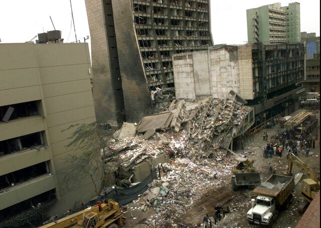 FILE - In this Aug. 8, 1998 file photo, the United States Embassy, left, and other damaged buildings in downtown Nairobi, Kenya, are shown on the day after it was bombed by terrorists. Some of the victims of the bombing will be in Washington on Monday, Feb . 24, 2020, to hear arguments in a Supreme Court case that could affect the compensation they ultimately receive for their injuries. (AP Photo/Dave Caulkin, File)