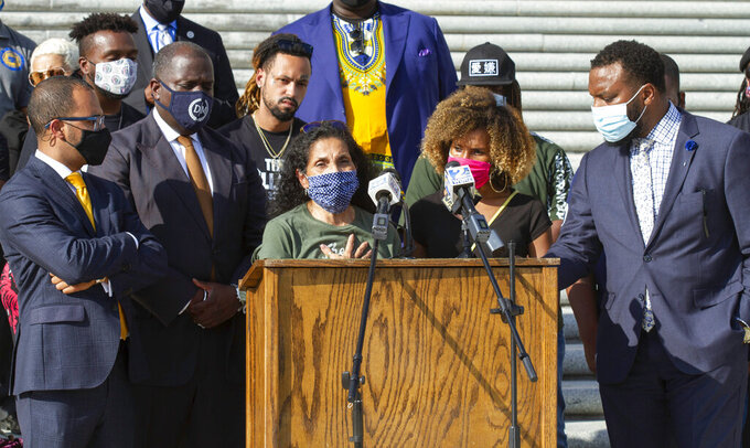 """FILE - In this Oct. 7, 2020, file photo, Mona Hardin, center left at podium, mother of Ronald Greene, speaks at a news conference outside the Louisiana State Capitol in Baton Rouge, La. Greene died following a police chase in Louisiana in 2019, and his death is now under federal investigation. Greene's family filed a federal wrongful-death lawsuit in May alleging troopers """"brutalized"""" Greene, used a stun gun on him three times and """"left him beaten, bloodied and in cardiac arrest,"""" before covering up his actual cause of death. (AP Photo/Dorthy Ray, File)"""