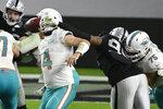 Ryan Fitzpatrick, quarterback de los Dolphins de Miami, es sujetado de la máscara por Arden Key, de los Raiders de Las Vegas, en el encuentro del sábado 26 de diciembre de 2020 (AP Foto/David Becker)