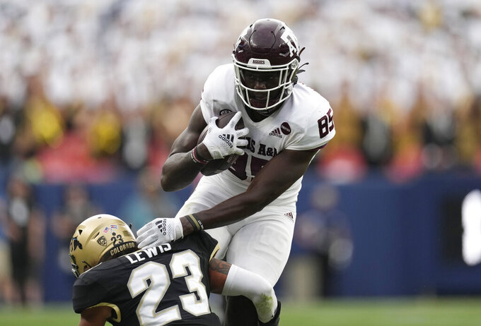 Colorado safety Isaiah Lewis, left, tackles Texas A&M tight end Jalen Wydermyer aftwer he pulled in a pass in the second half of an NCAA college football game Saturday, Sept. 11, 2021, in Denver. Texas A&M won 10-7. (AP Photo/David Zalubowski)