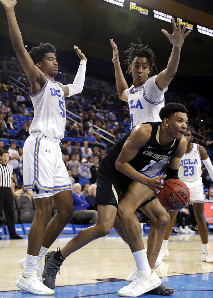 Colorado's Tyler Bey, center, is defended by UCLA center Moses Brown, right, and guard Chris Smith (5) during the first half of an NCAA college basketball game Wednesday, Feb. 6, 2019, in Los Angeles. (AP Photo/Marcio Jose Sanchez)