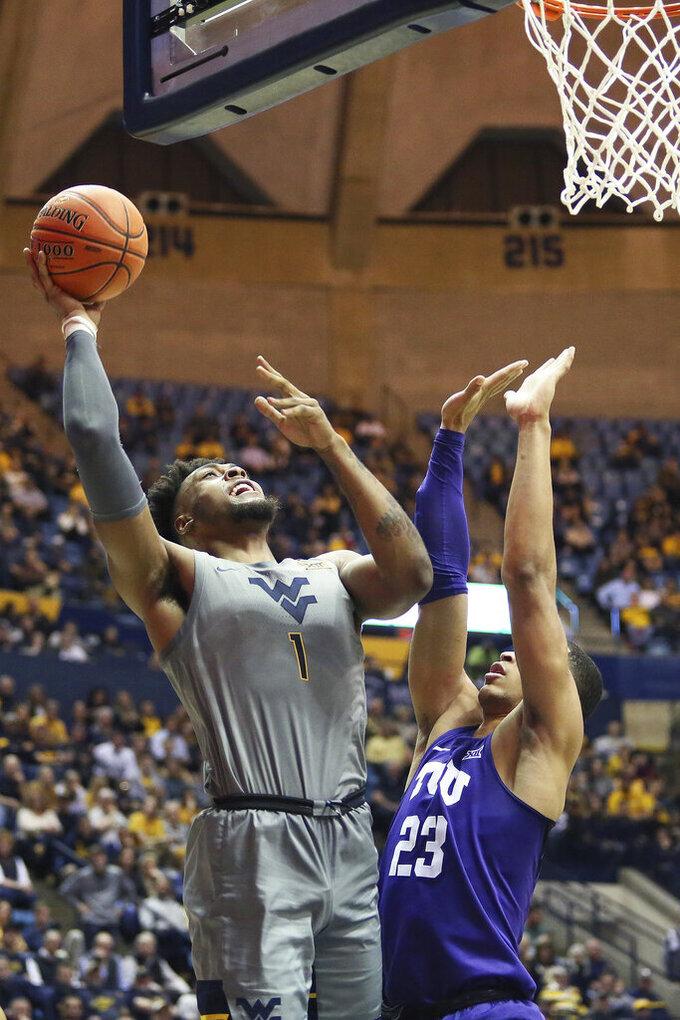 West Virginia forward Derek Culver (1) shoots as TCU forward Jaedon LeDee (23) defends during the second half of an NCAA college basketball game Tuesday, Jan. 14, 2020, in Morgantown, W.Va. (AP Photo/Kathleen Batten)
