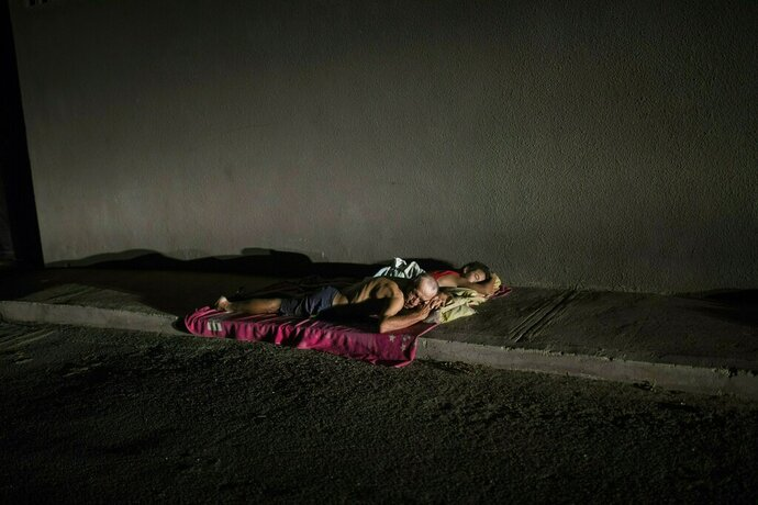 In this May 15, 2019 photo, people sleep on the sidewalk to escape from the heat, due to the lack of electricity in their homes that does not allow them to run their air conditioners and fans, during a blackout in Maracaibo, Venezuela. Maracaibo's sweltering heat approaches 100 degrees (37 centigrade) most days, making the air conditioner a must. (AP Photo/Rodrigo Abd)