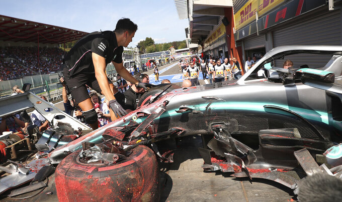 Pit crew inspect the damaged car of Mercedes driver Lewis Hamilton of Britain after Hamilton hit a barrier during the third practice session ahead of the Belgian Formula One at Spa-Francorchamps, Belgium, Saturday, Aug. 31, 2019. The Belgian Formula One race will take place on Sunday. (AP Photo/Francisco Seco)