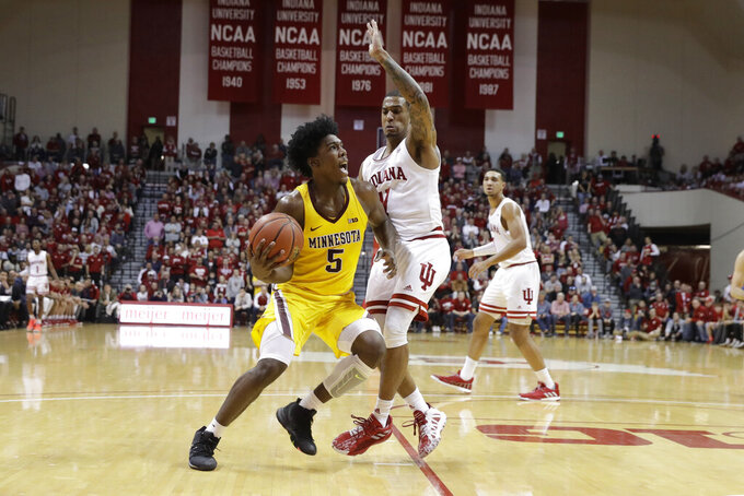 Minnesota's Marcus Carr (5) goes to the basket against Indiana's Devonte Green (11) during the first half of an NCAA college basketball game, Wednesday, March 4, 2020, in Bloomington, Ind. Indiana defeated Minnesota 72-67. (AP Photo/Darron Cummings)