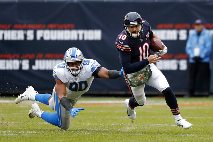 Chicago Bears quarterback Mitchell Trubisky (10) avoids a tackle byf Detroit Lions defensive end Trey Flowers (90) during the second half of an NFL football game in Chicago, Sunday, Nov. 10, 2019. (AP Photo/Charles Rex Arbogast)