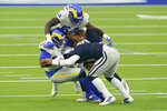 Dallas Cowboys quarterback Dak Prescott, right, is tackled by Los Angeles Rams defensive end Aaron Donald, left and outside linebacker Leonard Floyd (54) top during the first half of an NFL football game Sunday, Sept. 13, 2020, in Inglewood, Calif. (AP Photo/Ashley Landis )