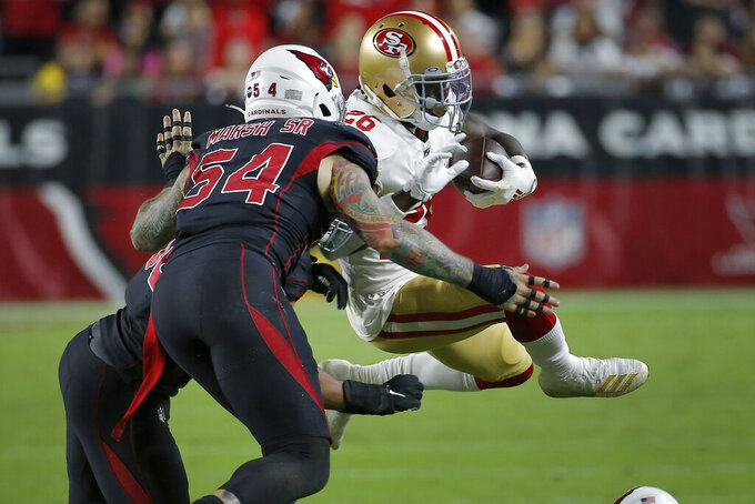 San Francisco 49ers running back Tevin Coleman (26) is hit by Arizona Cardinals middle linebacker Jordan Hicks and linebacker Cassius Marsh (54) during the second half of an NFL football game, Thursday, Oct. 31, 2019, in Glendale, Ariz. (AP Photo/Rick Scuteri)