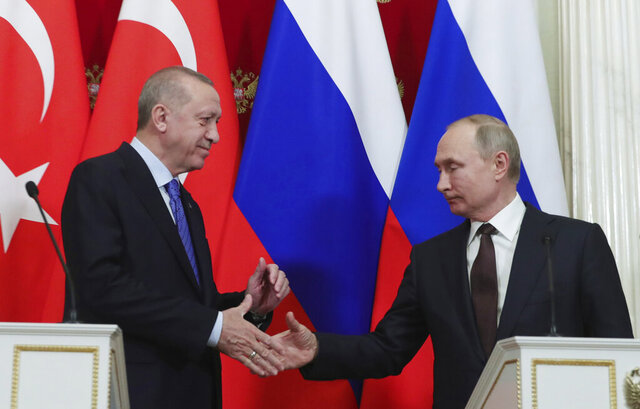Russia's President Vladimir Putin, right, and Turkish President Recep Tayyip Erdogan shake hands after a joint news conference followed six-hour talks in the Kremlin, in Moscow, Russia, Thursday, March 5, 2020. (Presidential Press Service via AP, Pool)