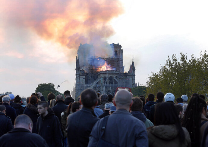 FILE - In this Monday, April 15, 2019 file photo, people watch as flames and smoke rise from Notre Dame cathedral in Paris. On Friday, April 19, 2019, The Associated Press has found that stories circulating on the internet that a Muslim woman in Paris was arrested for planning a terrorist attack at the cathedral, days before the fire, are untrue. Paris police investigators have said they think an electrical short-circuit most likely caused the fire. (AP Photo/Thibault Camus)