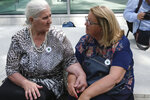 Munira Subasic, left, and Nermina Lakota, of the Mothers of Srebrenica organization, sit outside the Dutch Supreme Court, in The Hague, on Friday July 19, 2019, after the court issued a ruling in their case against the Dutch state.  The Dutch Supreme Court has upheld a lower court's ruling that the Netherlands is partially liable in the deaths of some 350 Muslim men who were murdered by Bosnian Serb forces during the 1995 Srebrenica massacre. (AP Photo/Michael Corder)