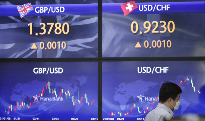 An employee of a bank walks near the screens showing the foreign exchange rates at the foreign exchange dealing room in Seoul, South Korea, Thursday, April 15, 2021. Asian stock markets were mixed Thursday after Wall Street retreated from a record high as major banks reported strong profits at the start of U.S. earnings season. (AP Photo/Lee Jin-man)