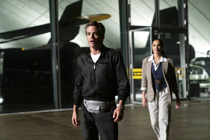 """This image released by Warner Bros. Entertainment shows Chris Pine, center, and Gal Gadot in a scene from """"Wonder Woman 1984."""" (Clay Enos/Warner Bros. Entertainment via AP)"""