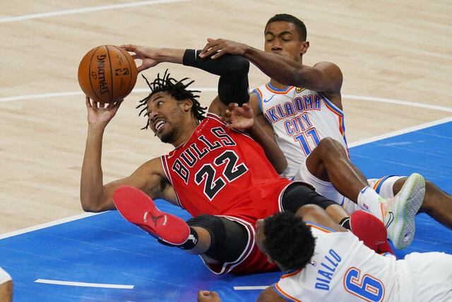 Chicago Bulls forward Otto Porter Jr. (22) passes in front of Oklahoma City Thunder guard Hamidou Diallo (6) and guard Theo Maledon (11) in the second half of a preseason NBA basketball game Wednesday, Dec. 16, 2020, in Oklahoma City. (AP Photo/Sue Ogrocki)