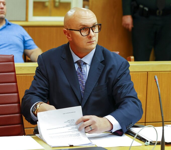 FILE- In this June 22, 2021, file photo, William Braddock looks through papers during a hearing, Tuesday, in Clearwater, Fla. Anna Paulina Luna, who plans to run for Florida's District 13 seat after losing a race for the slot in 2020 to Democratic U.S. Rep. Charlie Crist, contends in court documents that GOP challenger William Braddock is stalking her and wants her dead. (Chris Urso/Tampa Bay Times via AP, File)