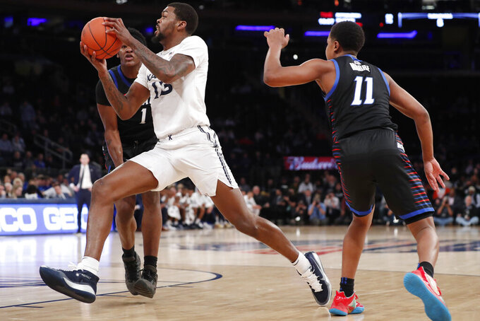 Xavier forward Naji Marshall (13) drives between DePaul guard Charlie Moore (11) and forward Romeo Weems (1) during the first half of an NCAA college basketball game in the first round of the Big East men's tournament Wednesday, March 11, 2020, in New York. (AP Photo/Kathy Willens)
