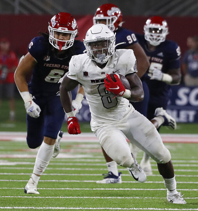 UNLV running back Charles Williams, center, runs past Fresno State defenders during the second half of an NCAA college football game in Fresno, Calif., Friday, Sept. 24, 2021. (AP Photo/Gary Kazanjian)