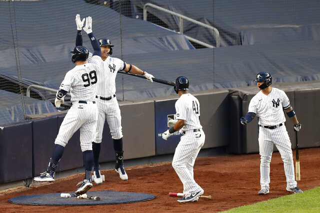 New York Yankees' Aaron Judge (99) celebrates with designated hitter and on-deck batter Giancarlo Stanton after hitting a three-run home run during the second inning of the team's baseball game against the Boston Red Sox, Sunday, Aug. 2, 2020, at Yankee Stadium in New York. (AP Photo/Kathy Willens)
