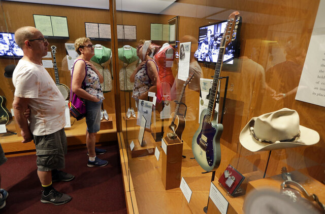 FILE - In this May 25, 2018 photo, visitors to the Country Music Hall of Fame and Museum in Nashville, Tenn. view the the Outlaws & Armadillos exhibit. The NRA has been publicizing plans to auction off firearms at a fundraising dinner at the Country Music Hall of Fame and Museum. But a spokesperson for the museum tells The Associated Press that the April event will not take place there after the AP asked questions about the museum's no firearms policy. (AP Photo/Mark Humphrey, File)