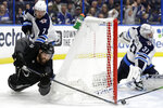 Tampa Bay Lightning left wing Pat Maroon (14) is taken down by Winnipeg Jets defenseman Dmitry Kulikov (7) as he tries to wrap the puck past goaltender Connor Hellebuyck (37) during the second period of an NHL hockey game Saturday, Nov. 16, 2019, in Tampa, Fla. (AP Photo/Chris O'Meara)
