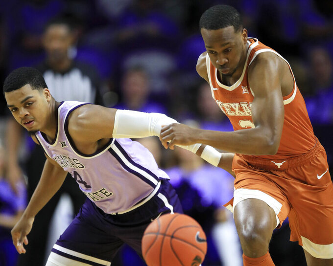 Texas guard Matt Coleman III, right, steals the ball from Kansas State guard David Sloan, left, during the first half of an NCAA college basketball game in Manhattan, Kan., Saturday, Feb. 22, 2020. (AP Photo/Orlin Wagner)