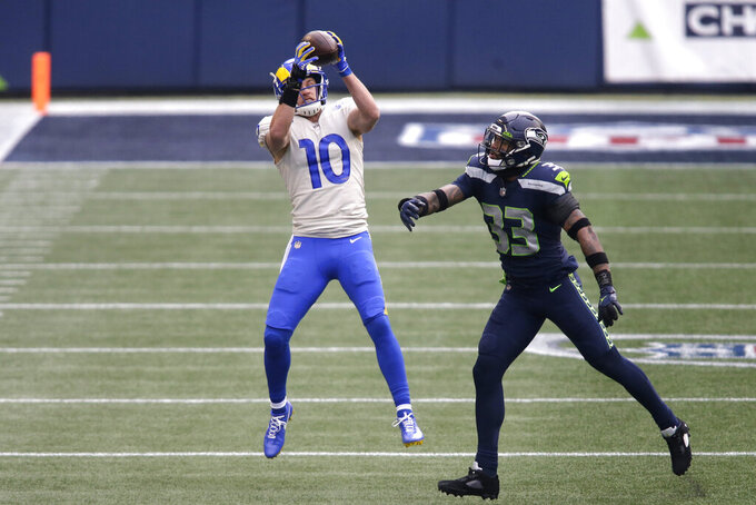 Los Angeles Rams wide receiver Cooper Kupp (10) leaps to make a catch in front of Seattle Seahawks strong safety Jamal Adams during the first half of an NFL wild-card playoff football game, Saturday, Jan. 9, 2021, in Seattle. (AP Photo/Scott Eklund)