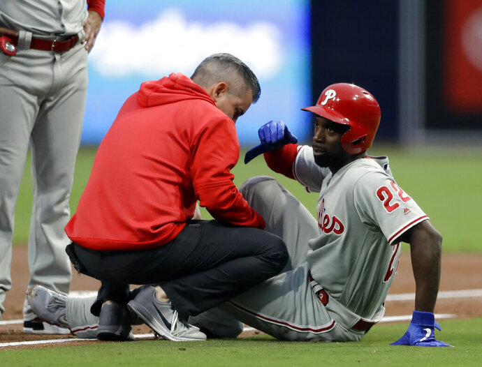 FILE - In this June 3, 2019, file photo, Philadelphia Phillies' Andrew McCutchen, right, is helped by a trainer after injuring his knee while trying to get back to first base during the first inning of a baseball game against the San Diego Padres in San Diego. McCutchen says he plans to be ready for opening day after the injury cut short his 2019 season. (AP Photo/Gregory Bull, File)