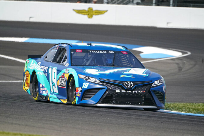 Martin Truex Jr. (19) drives through a turn during practice for the NASCAR Cup Series auto race at Indianapolis Motor Speedway in Indianapolis, Saturday, Aug. 14, 2021. (AP Photo/Michael Conroy)