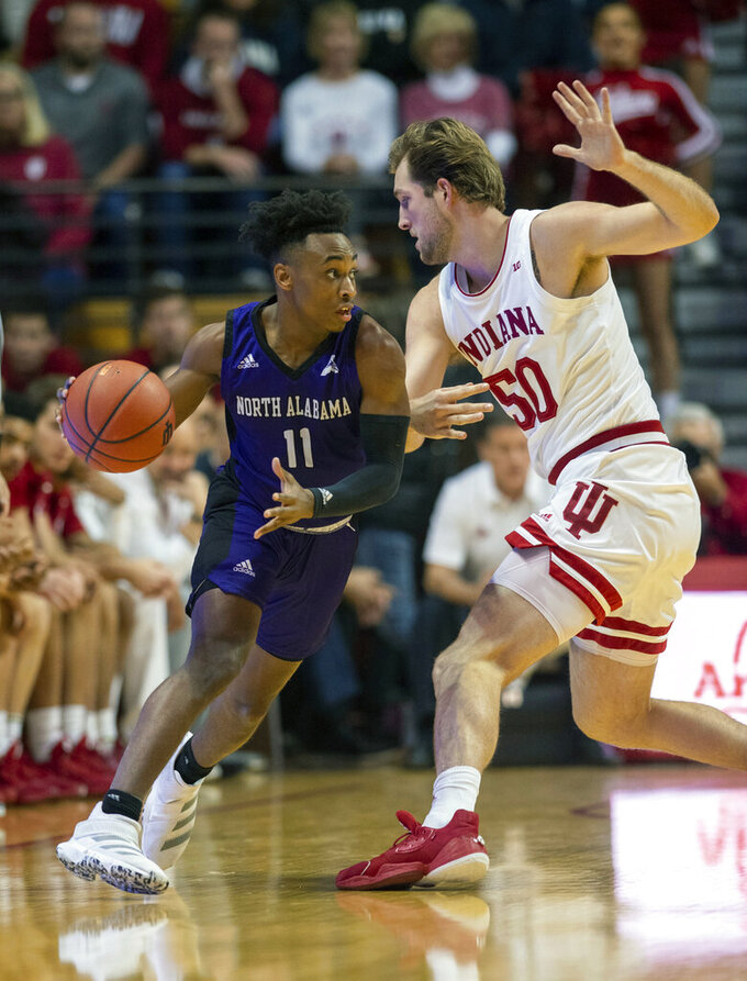 North Alabama's C.J. Brim (11) works the ball around the court as he's defended by Indiana's Joey Brunk (50) during the first half of an NCAA college basketball game, Tuesday, Nov. 12, 2019, in Bloomington, Ind. (AP Photo/Doug McSchooler)