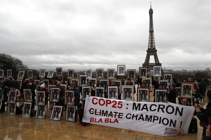 A hundred activists hold portraits of President Emmanuel Macron to urge France to take action during the U.N. COP 25 climate talks in Madrid, during a gathering at Place du Trocadero facing the Eiffel Tower in Paris, Sunday, Dec. 8, 2019. Environmental activists around France have removed President Emmanuel Macron's official portrait from town halls around the country in an unusual protest movement aimed at pushing him to do more to slow climate change. (AP Photo/Francois Mori)