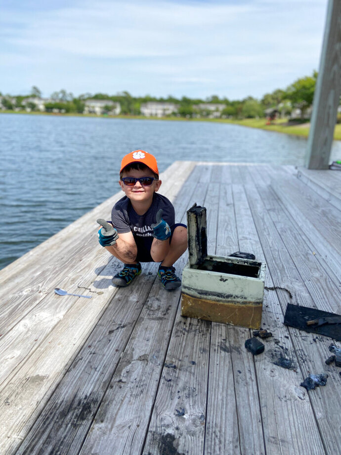 In this May 9, 2020, photo provided by Catherine Brewer, Knox Brewer poses next to a safe he pulled out of Whitney Lake in South Carolina. The 6-year-old was using a magnet attached to a string to fish for metal in the water when he reeled in a lockbox that police said was stolen from a woman who lived nearby eight years ago. (Catherine Brewer via AP)
