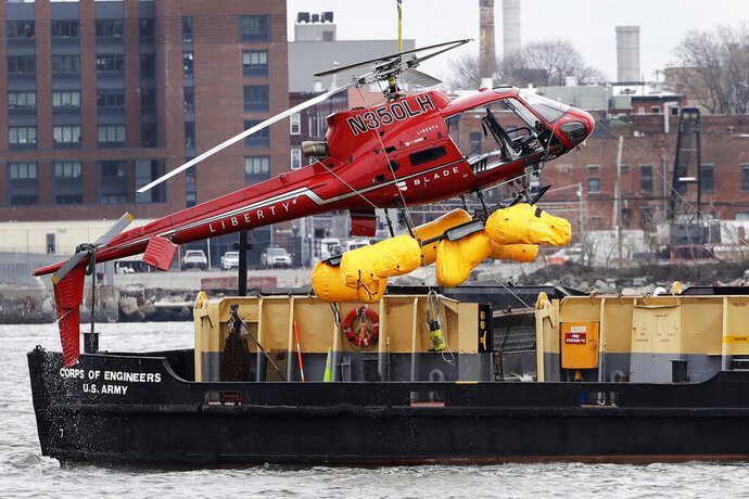 FILE - In this March 12, 2018 file photo, a helicopter, which crashed the previous day, is hoisted by crane from the East River onto a barge, in New York. The helicopter company, FlyNYON, exploited a regulatory loophole to avoid stricter safety requirements, federal investigators said Tuesday, Dec. 10, 2019. (AP Photo/Mark Lennihan, File)