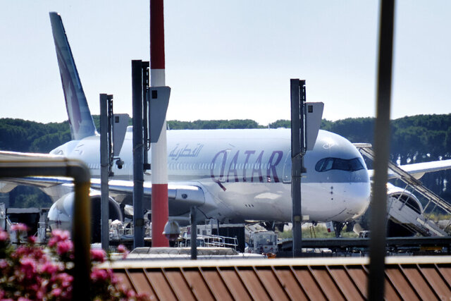 A Qatar Airways aircraft is parked at Rome's Leonardo Da Vinci international airport, Wednesday, July 8, 2020. Rome airport authorities have refused to let 112 Bangladeshi passengers off a plane that landed from Qatar as Italy tightens restrictions on people arriving from coronavirus hotspots. The 112 Bangladeshis were among 205 passengers who arrived Wednesday aboard a Qatar Airways flight that originated in Pakistan and stopped in Doha, Qatar. (Mauro Scrobogna/LaPresse via AP)