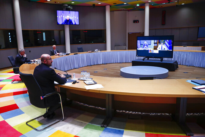 European Council President Charles Michel, left, talks during a video conference with the leaders of Germany, France, Portugal and Greece, on the screen, ahead of the EU summit at the European Council headquarters in Brussels, Tuesday, March 23, 2021. (AP Photo/Francisco Seco, Pool)
