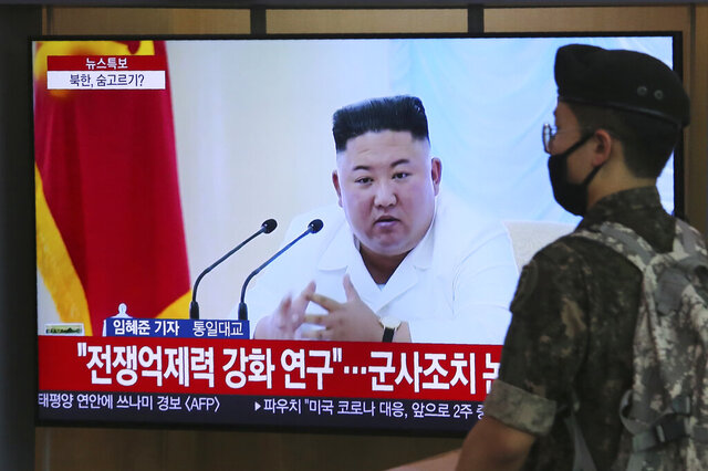 A South Korean army soldier passes by a TV showing a file image of North Korean leader Kim Jong Un during a news program at the Seoul Railway Station in Seoul, South Korea, Wednesday, June 24, 2020. Kim suspended his military's plans to take unspecified retaliatory action against South Korea, state media said Wednesday, possibly slowing a pressure campaign against its rival amid stalled nuclear negotiations with the Trump administration. The Korean letters read: