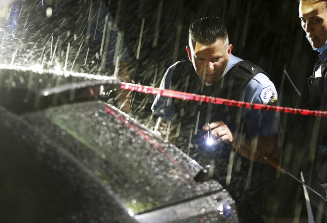 Police look at bullet holes on an SUV wherein a 3-year-old boy was fatally shot while riding in the vehicle with his father, outside West Suburban Medical Center Saturday, June 20, 2020, in Oak Park in Chicago. The boy was struck in the 5600 block of West Huron Street in the Austin neighborhood, and his father drove to the hospital, where he was pronounced dead. Multiple people, including several children, were killed as more than 100 people were shot in a wave of gunfire in Chicago over the Father's Day weekend that produced the city's highest number of shooting victims in a single weekend this year. (John J. Kim/Chicago Tribune via AP)