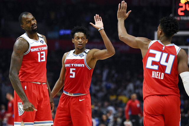 Sacramento Kings guard De'Aaron Fox, center, celebrates with guard Buddy Hield, right as center Dewayne Dedmon watches during the second half of an NBA basketball game against the Los Angeles Clippers in Los Angeles, Thursday, Jan. 30, 2020. The Kings won 124-103. (AP Photo/Kelvin Kuo)