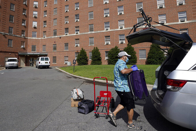 A parent packs a student's belongings at Ehringhaus dormitory following a cluster of COVID-19 cases on campus at the University of North Carolina in Chapel Hill, N.C., Tuesday, Aug. 18, 2020. The university announced that it would cancel all in-person undergraduate learning starting on Wednesday causing some students to pack and leave. (AP Photo/Gerry Broome)