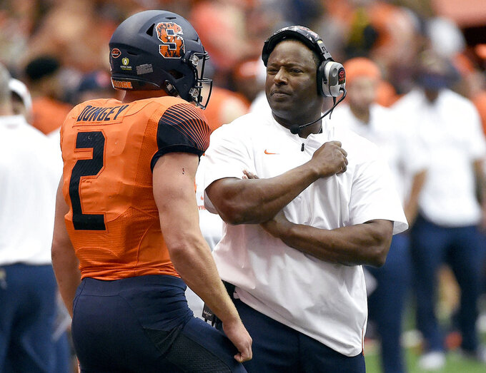 FILE - In this Sept. 22, 2018, file photo, Syracuse coach Dino Babers talks with quarterback Eric Dungey (2) during an NCAA college football game against Connecticut, in Syracuse, N.Y. Coach Babers has led Syracuse to a surprising 4-2 record midway through the season, while Clemson and North Carolina State, led by quarterback Ryan Finley, are undefeated entering a big showdown this week. All drew attention in midseason voting by AP writers covering the 14 ACC teams. (Dennis Nett/The Post-Standard via AP, File)