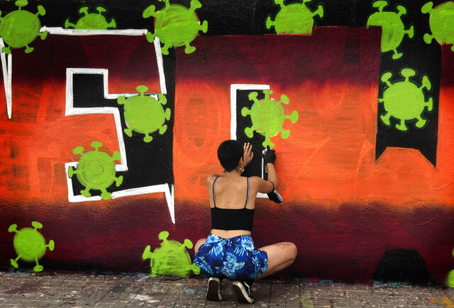 An artist sprays paints a wall with topic about the Coronavirus in Barcelona, Spain, Thursday, Aug. 13, 2020. Spain's daily number of new COVID-19 cases has shot up, with almost 2,935 officially reported Thursday compared with 1,690 the previous day. (AP Photo/Emilio Morenatti)