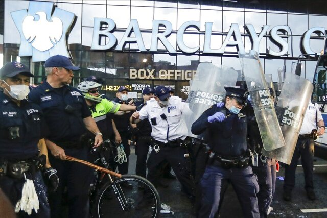 Police officers protect themselves with shields as protesters throw debris during a rally Friday, May 29, 2020, in the Brooklyn borough of New York, at the Barclays Center over the death of George Floyd, a black man who was in police custody in Minneapolis. (AP Photo/Frank Franklin II)