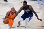 Phoenix Suns' Jevon Carter (4) drives past Dallas Mavericks' Michael Kidd-Gilchrist (9) during the second half of an NBA basketball game Thursday, Aug. 13, 2020 in Lake Buena Vista, Fla. (AP Photo/Ashley Landis, Pool)