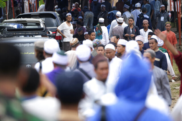 Pilgrims make their way through the crowd on a field where a mass congregation is supposed to be held in Gowa, South Sulawesi, Indonesia, Thursday, March 19, 2020. Indonesia halted the congregation of thousands of Muslim pilgrims and began quarantining and checking their health Thursday to prevent the spread of the new coronavirus. The vast majority of people recover from the new coronavirus. According to the World Health Organization, most people recover in about two to six weeks, depending on the severity of the illness. (AP Photo/Syaief)
